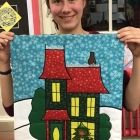 Emma Hill proudly displays her finished Christmas wall hanging in Region 14